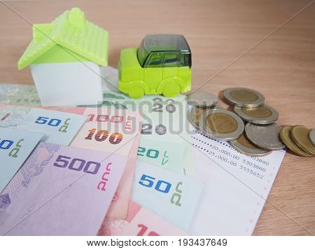 Saving money for car and house concept account banknotes coins on wooden background
