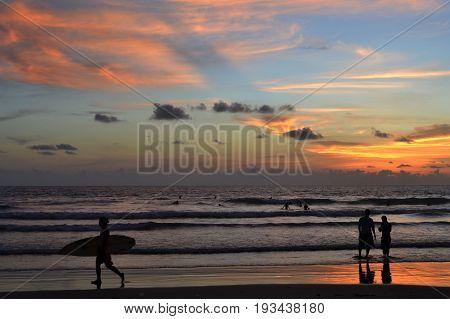 Surfer and sunset in Kuta, Bali, Indonesia
