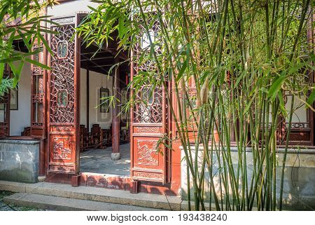 Suzhou, China - Nov 5, 2016: Master of Nets Garden (Wang Shi Yuan) - Doorway designed in the classical Chinese architecture style, with bamboo bush in front.