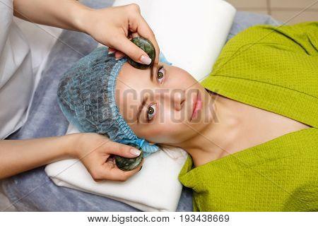 Spa treatment. Facial massage with jade stones. Alternative medicine. Massage of forehead zone. Guasha
