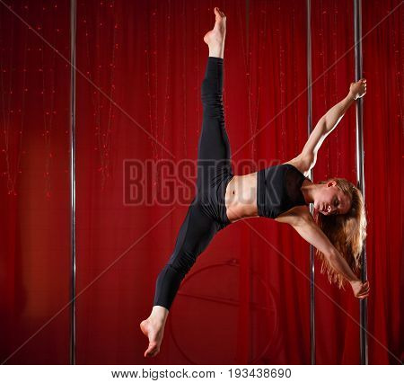 Sexy pole dancer sat on a string on a pylon. Flexibility and plasticity.