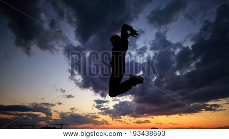 Silhouette of a man against a background of clouds and sunset. He is jumping on the roof. Parkour in the evening.