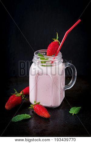 Yoghurt-strawberry Smoothies In A Jar On A Black Background