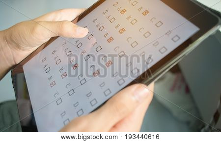 blurred of student testing in online exam in form exercise exams answer on tablet with multiple-choice quiz or questions by finger clicking