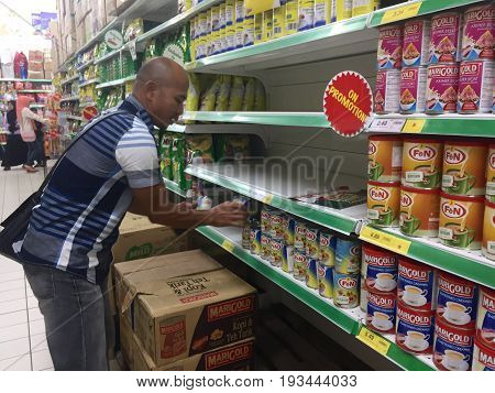 Keningau,Sabah-June 23,2017:Men choose household goods in a large store of Giant Malaysian Supermarket in Keningau,Sabah.Giant,pioneered the concept of modern supermarket shopping.