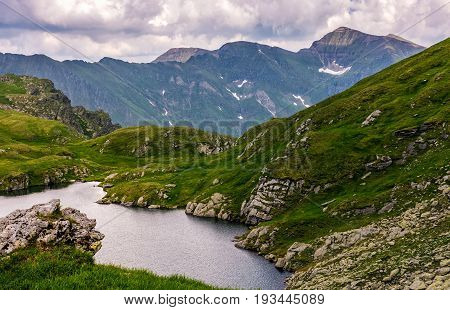 Lake In Mountains With Grass On Hillside