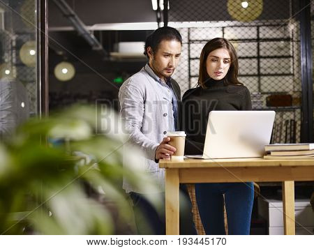 asian and caucasian employee in small private company working together using laptop computer.