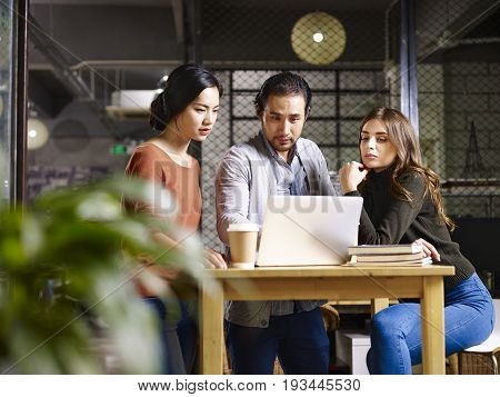 a team of asian and caucasian entrepreneurs working together in office using laptop computer.