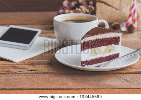 Banana chocolate cake on white plate served with black coffee. Chocolate cake layered with whipped cream and banana look so delicious. Enjoy during play smart phone with chocolate cake and coffee. Triangle slice piece of chocolate cake.