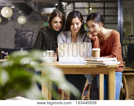 three female entrepreneur asian and caucasian working in office using laptop computer.