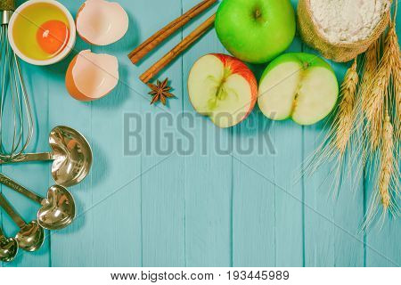 Bakery background comprise apples wheat flour egg cinnamon notebook and pencil on wood table with copy space.Prepare ingredient for baking apple cake on wood table. Bakery background top view concept. Apple cinnamon cake on blue background.