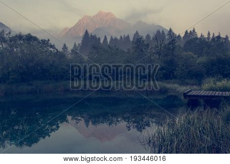 Morning mists rising above lake surrounded by mountains. Zelenci nature reserve near Kranjska Gora, Slovenia.