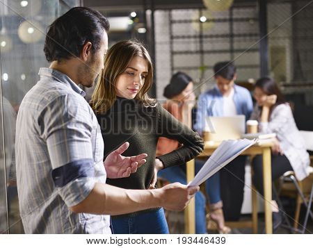 people in small start-up company discussing business in office.