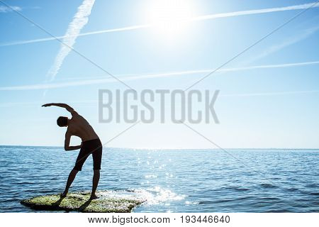 man making yoga exercise stand on big stone in the sea doring sunrise
