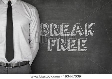 Midsection of businessman in shirt and tie standing by break free text on blackboard