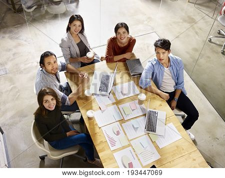 high angle view of a team of asian and caucasian business people looking at camera smiling.