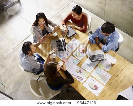high angle view of a team of asian and caucasian corporate executives discussing business in meeting room.
