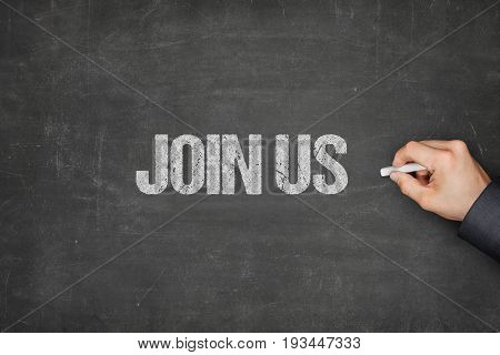 Cropped hand of businessman writing join us text on blackboard