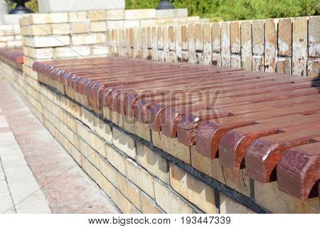 Wooden and brick bench in the garden patio.