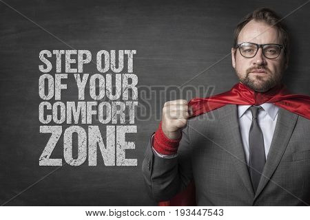 Determined businessman wearing cape standing by step out of your comfort zone text on blackboard