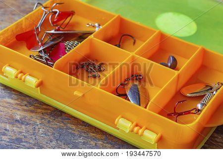 Metal Fishing Baits In A Orange Plastic Storage Box Closeup
