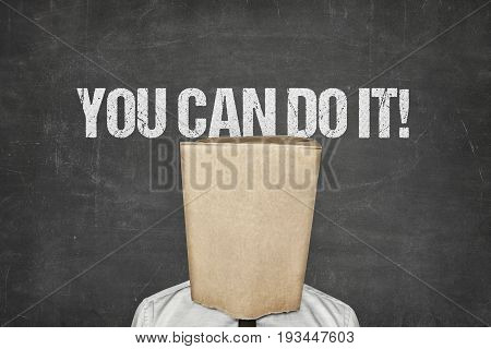 Businessman covering face with paperbag under you can do it text on blackboard
