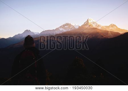 Hiker young man with backpack looking at mountains range that is in front of him. Trekker man trekking in Nepal trekking route around Himalaya Mountain. Tourist traveling in holiday in the beginning of winter.