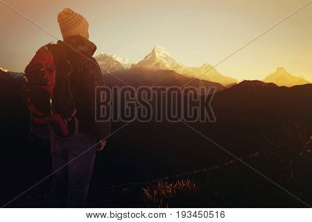Hiker man with backpack looking at sunrise and mountain range that is in front of him. Trekker man trekking in Nepal trekking route around Himalaya Mountain. Tourist traveling in holiday in the beginning of winter.