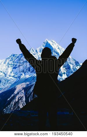Silhouette image of hiker young man with backpack looking at mountain range and put hands up. Trekker man trekking in Nepal trekking route around Himalaya Mountain. Tourist traveling in holiday in the beginning of winter.