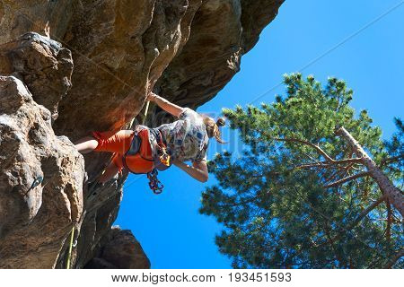 Female extreme climber conquers steep rock. Rock climber girl. Willpower success concept.