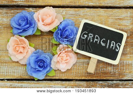 Gracias (which means thank you in Spanish) written on mini blackboard with colorful roses