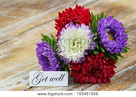 Get well card with colorful aster flowers bouquet on rustic wooden surface
