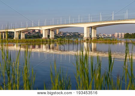 Modern bridge over river Angara in Irkutsk city in the evening with green grass at foreground