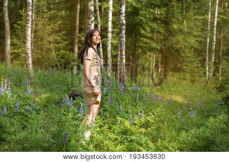 Young girl in a forest park whirl dances among flowers and birch trees