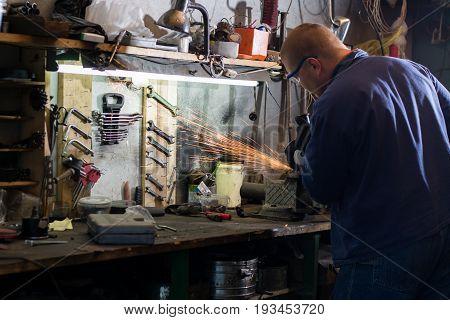 Photo of mechanic grinding metal plate in workshop