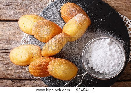 Golden Cookies Madeleine Sprinkled With Powdered Sugar Close-up On The Table. Horizontal Top View