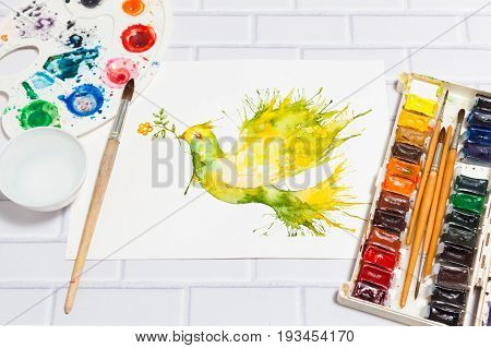 Hand drawn watercolor sketch with green dove flying with flower branch and leaves.Paints, paintbrushes and palette on the white brick background - concept of human creativity, perspective close up view