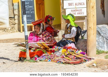 OLLANTAYTAMBO, PERU - 27 APRIL 2017: Woman with children weaving on the streets of the small, medieval city of Ollantaytambo
