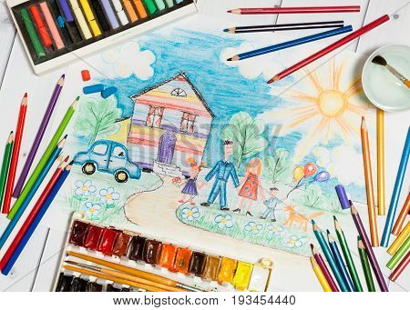 Hand drawn Bright Colorful Childrens Sketch With Happy Family, House, Dog, Car on the Lawn with Flowers with lying flat pencils, paints and pastel - concept of children creativity, close up top flat view