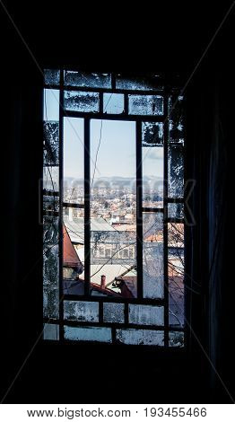 A smashed smoked window of an old house at the center of Tbilisi and a view to the city.