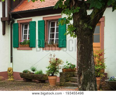 A Traditional German House With White Walls, Green Shutters And Tile Roof, A Yard With Flower Pots A