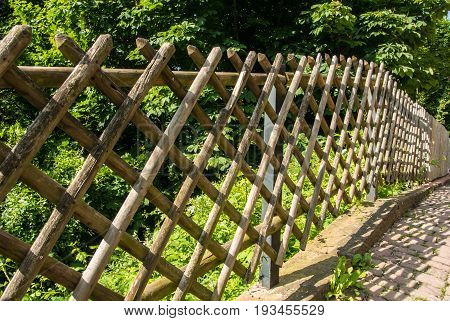 Beautiful Wooden Fence Near The Rural Country Path On Sunny Summer Day With Green Golliage At The Ba