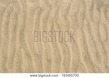 A Sand Texture, Close-up Macro View To A Sand Of A Beach With Shapes, Waves And Lines Formed By The