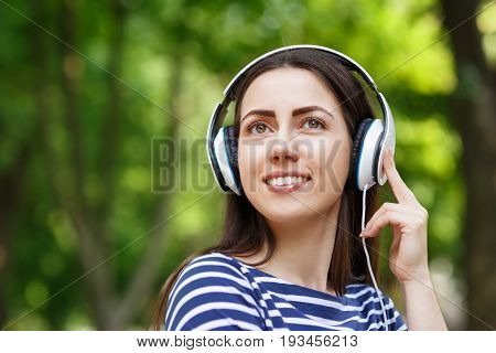 young happy smiling brunette woman with headphones outdoors on summer day. Girl listening music in headphones in park. Portrait of woman at outdoor with headphones