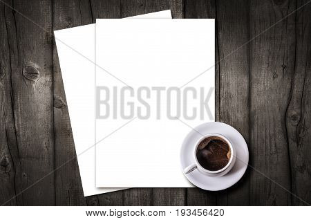 Blank letterhead and coffee cup on vintage wooden table background. Blank branding template. Mockup for branding identity for placing your design. Top view.