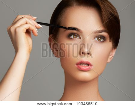 Beautiful Young Woman Applying Foundation On Her Face With A Make Up Brush Isolated On Gray Backgrou