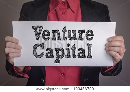Venture capital message on white card hold by businessman