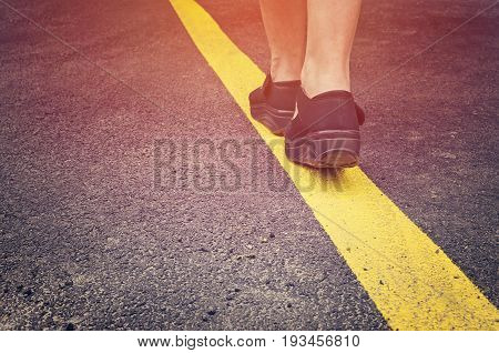 Woman walking on the yellow street line