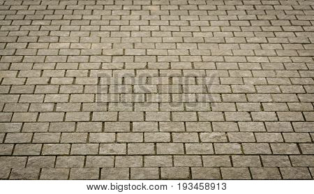 Brown Stone pavement texture. Granite cobblestoned pavement in perspective for background.