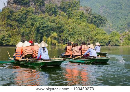 International tourists traveling on local vietnamese small boat along the Ngo Dong river of the Tam Coc Ninh Binh Vietnam.